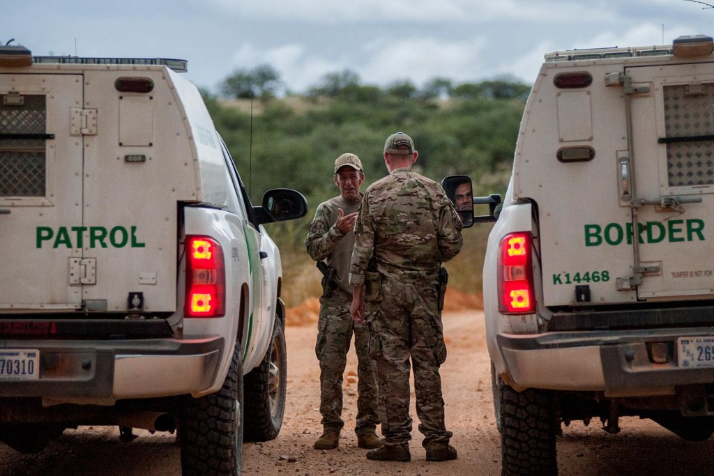 OCTOBER 7 2014 SASABE ARIZONA- Nailer (Middle left) and Spartan (middle right) talks with Border Patrol agents.