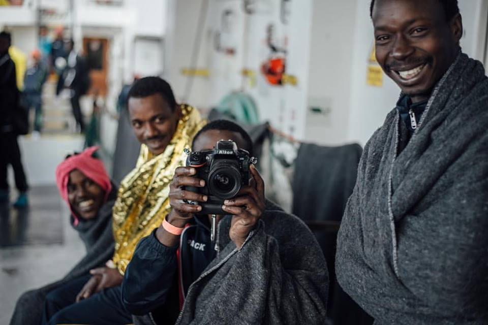 Alcuni migranti, appena soccorsi, si abbandonano a un momento di divertimento