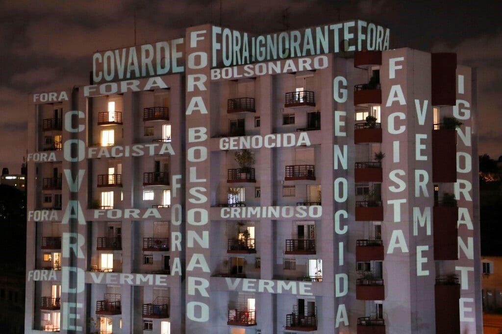 """La parole """"fuori Bolsonaro, codardo, fascista, ignorante, genocida, verme, criminale"""" proiettate su un edificio di São Paulo. (foto di Amanda Perobelli)"""